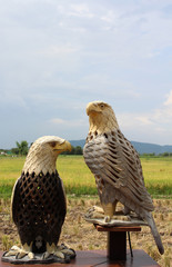 Two eagles wood carving standing on wooden floor and wood stick.