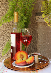 Glass of pink  wine and peaches .