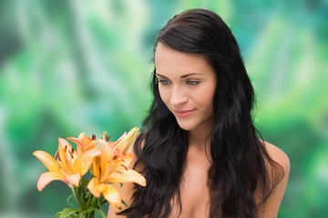 Beautiful nude brunette smiling at bunch of lilies