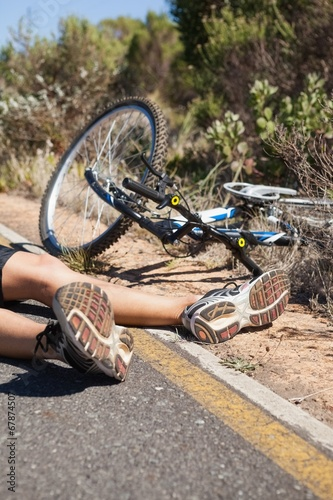 Cyclist lying on the road after an accident - 67874507