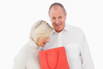 Older couple holding red gift bag