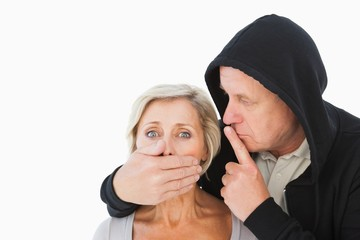 Older man silencing his fearful partner