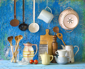 various vintage kitchen utensils,against blue wall