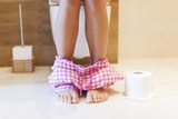 Woman using toilet in morning