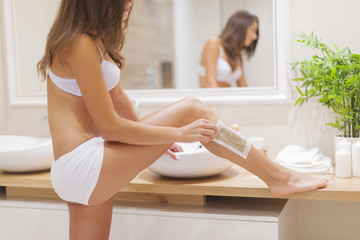 Focus woman waxing leg in bathroom