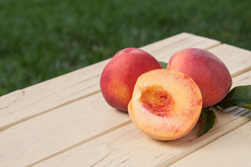 Fresh organic peaches on a yellow rustic table - side view