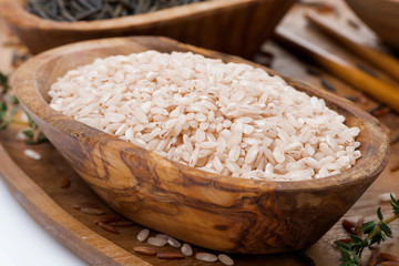 pink unpolished rice in a wooden bowl, close-up