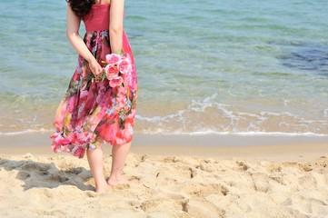 海とピンクの服を着て花束を持っている女性
