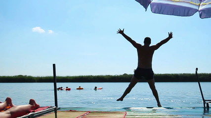 Young man jumping in lake, Slow motion.