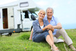 Happy senior couple sitting in grass, camper in background - 67881194