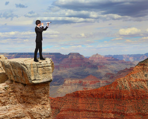 business man looks through telescope on mountain