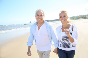 Senior couple running on a sandy beach
