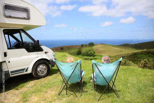Senior couple relaxing in camping folding chairs, sea landscape - 67881153