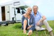 Leinwanddruck Bild - Happy senior couple sitting in grass, camper in background