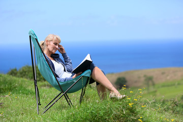 Senior woman reading book on hill by the sea