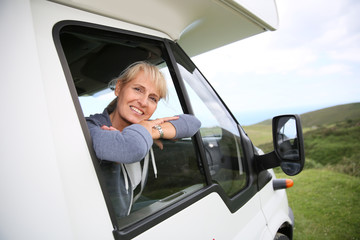 Happy senior woman by motorhome window