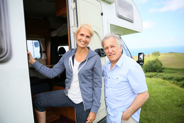 Senior couple climbing camper door steps
