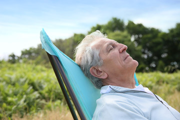 Closeup of senior man relaxing in camping chair