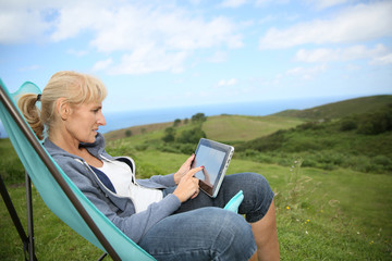 Senior woman weburfing on digital tablet, relaxing in chair