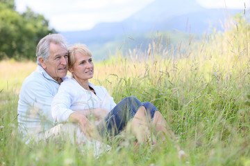 Senior couple relaxing in wild grass field