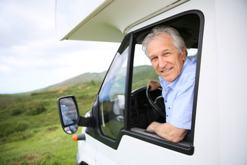 Senior man in motorhome sitting by steering wheel