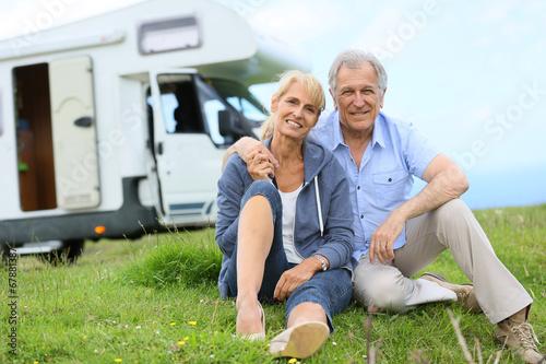 Leinwanddruck Bild Happy senior couple sitting in grass, camper in background