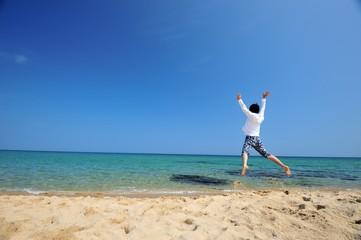 誰もいないビーチと白いシャツの男性