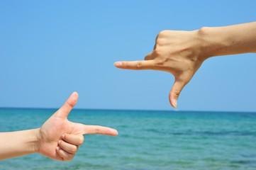 海をフォーカスして構図を決めている手