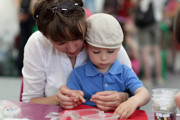 Mother with son making bracelet