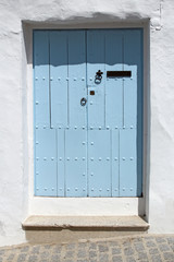 wooden blue door and whitewashed wall