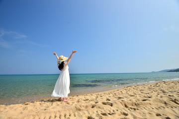 麦わら帽子と白いドレスを着てビーチに立っているアジア人女性の後ろ姿
