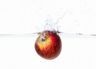 apple dropped into water splash on white