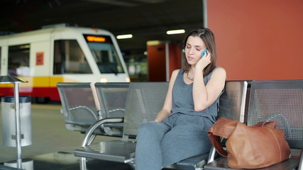 Angry, late woman talking on cellphone at train station