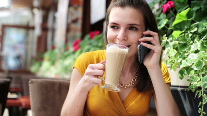 Elegant woman talking on cellphone, drinking coffee in cafe