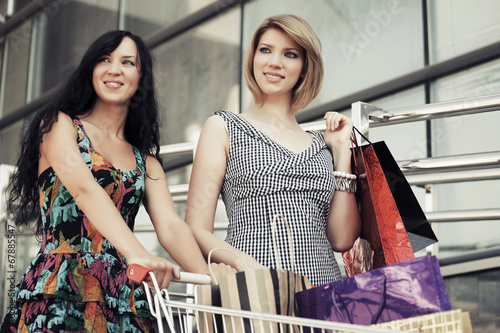 Two young fashion women with shopping cart in the mall
