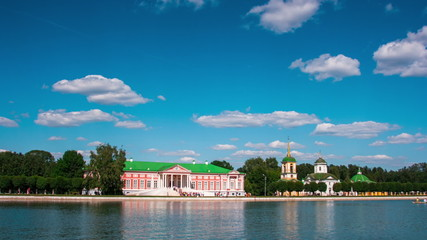 Kuskovo palace and pond with boats in the sunny summer day, time
