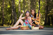 canvas print picture - Two hippie girls with guitar in a summer forest