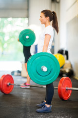 Female Athlete Lifting Barbell At Gym