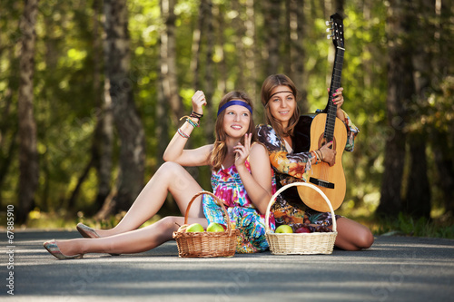 canvas print picture Two hippie girls with guitar in a summer forest