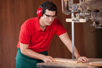 Carpenter Cutting Plank With Bandsaw