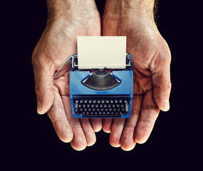blue typewriter in hands