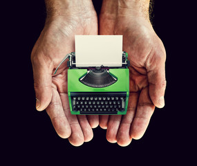 green typewriter in hands
