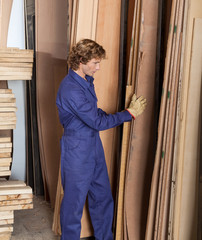 Carpenter Arranging Wooden Planks In Workshop