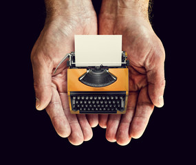 orange typewriter in hands