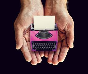 pink typewriter in hands