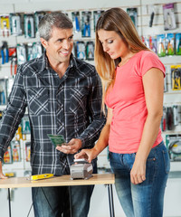 Couple Paying Through Smartphone In Hardware Store