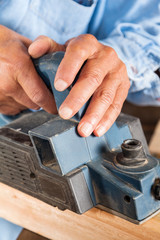 Carpenter's Hands Shaving Wood With Electric Planer