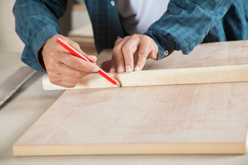 Male Carpenter Marking On Wood With Pencil