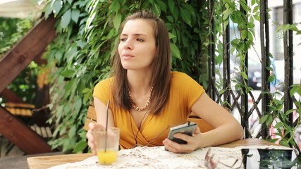 Woman listen to music on smartphone, drinking juice in cafe