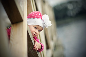Little girl looking through footbridge balustrade